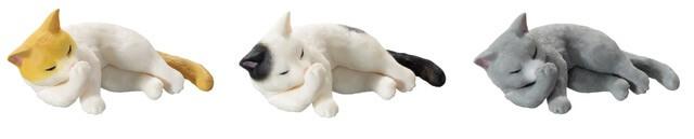 横たわったまま手を毛づくろいする猫のフィギュア