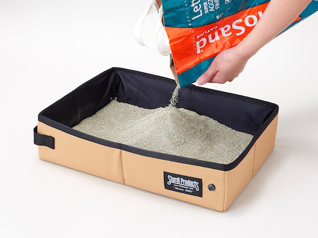 携帯用の猫トイレ「サンドボックス」に猫砂を注ぐイメージ