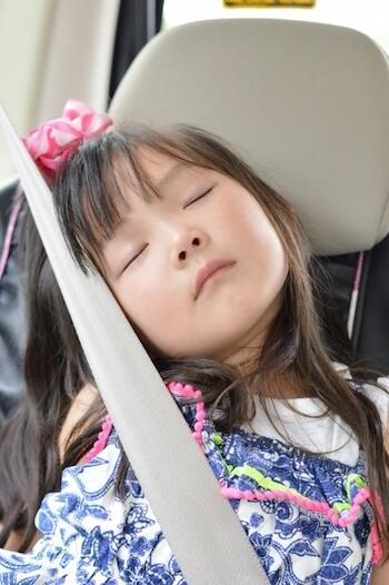 車内でシートベルトにもたれて眠る女の子
