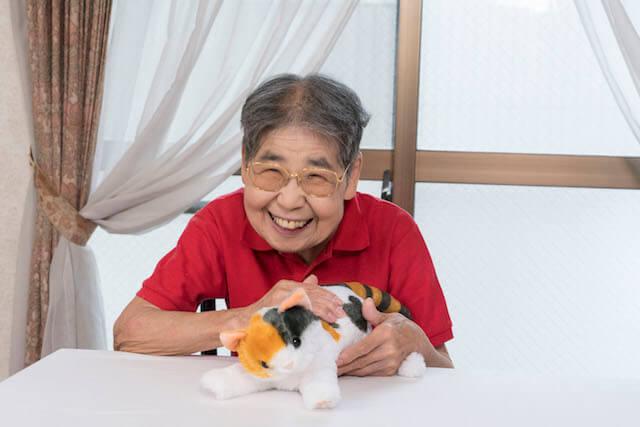 老人ホームの実験でも効果が見られた、猫のぬいぐるみ「なでなでねこちゃん」を撫でるおばあちゃん