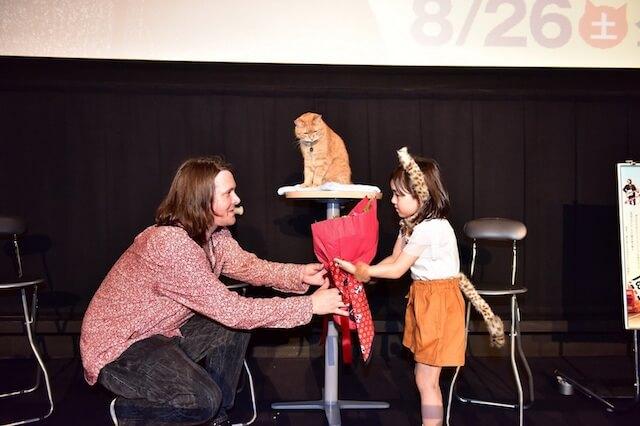 ジェームズと茶トラ猫のボブにプレゼントを渡す子役の新津ちせ