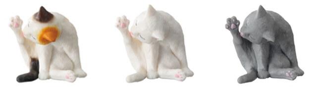 足を伸ばして毛づくろいする猫のフィギュア