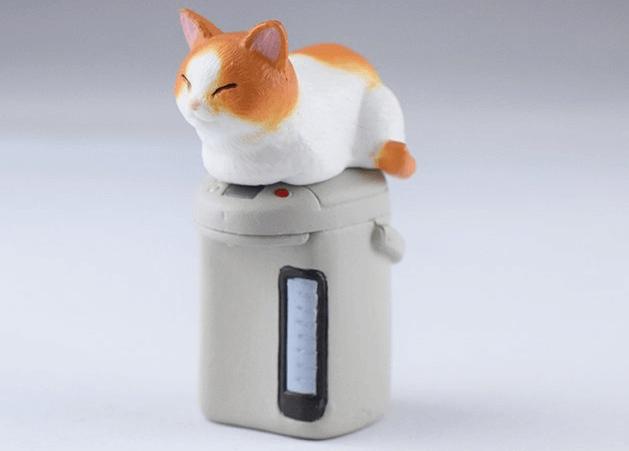 給湯ポットに乗る茶白猫のフィギュア