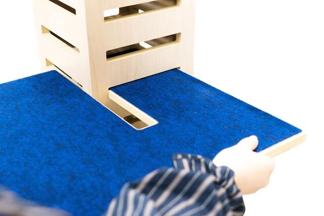 キャットタワー「necobacoT」のインディゴカラー(藍色)にコの字型ステップを差し込む様子