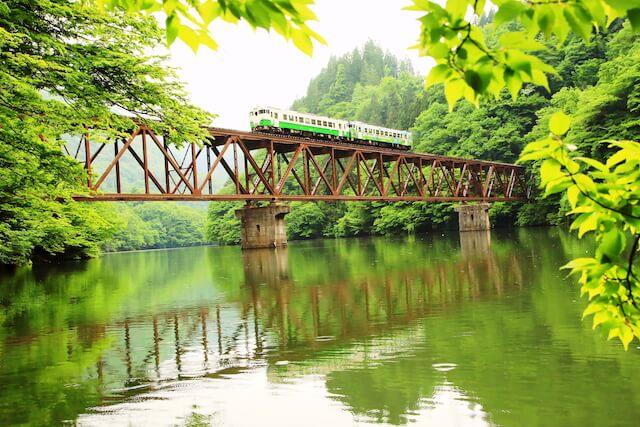 星賢孝さんの鉄道写真、緑に囲まれた鉄橋の上を走る鉄道