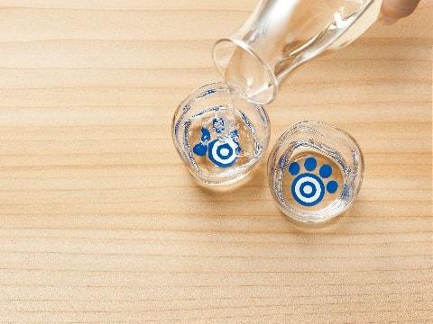 猫の肉球お猪口に、日本酒を注ぐイメージ