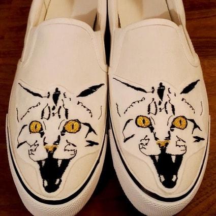 靴の甲部分に猫がデザインされたスニーカー