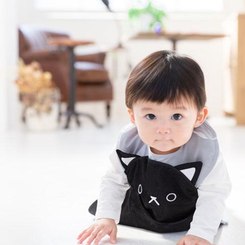 黒猫デザインのお食事エプロン「aboo(アブー)を着てハイハイする子ども