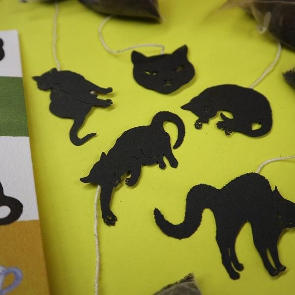 黄色のカラー用紙の上に置いた「ね紅茶」の猫の切り絵タグ