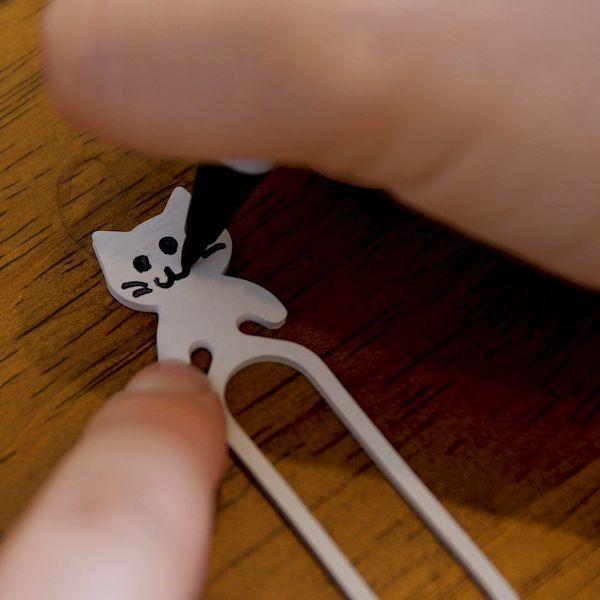 猫型ゴムバンド「Qutto(きゅっと)に猫の顔を書き込んでいる様子