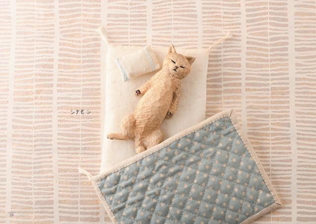 布団で寝る猫の木彫り作品 by はしもとみお