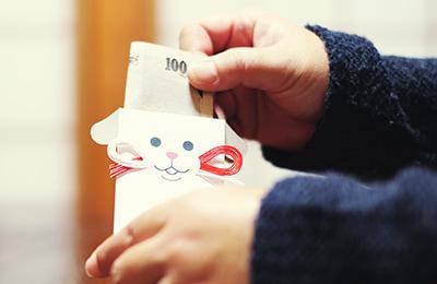 ポチ袋「タマ吉&ポチ福」にお年玉を入れるイメージ