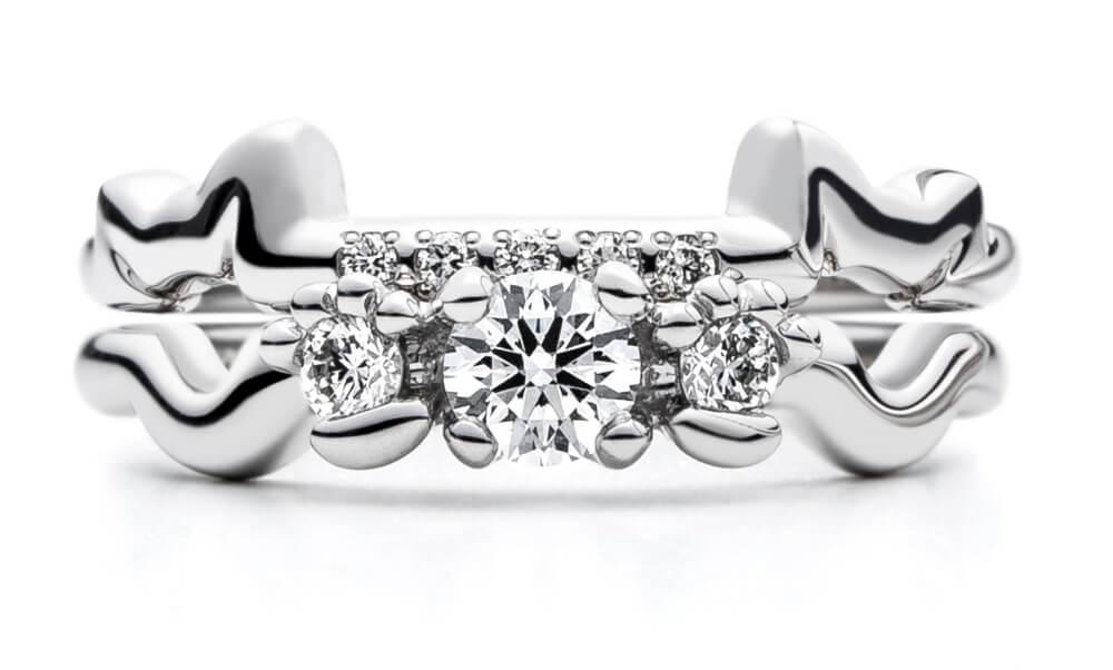 結婚指輪と婚約指輪「N.E.K.O(ネコ)」を重ねて猫が現れたイメージ by AFFLUX
