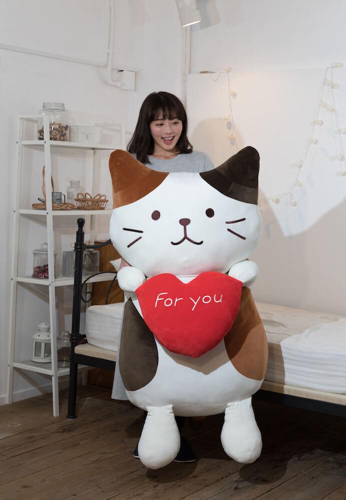 「Fuku Fuku にゃんこ」の巨大ぬいぐるみを抱き上げたイメージ