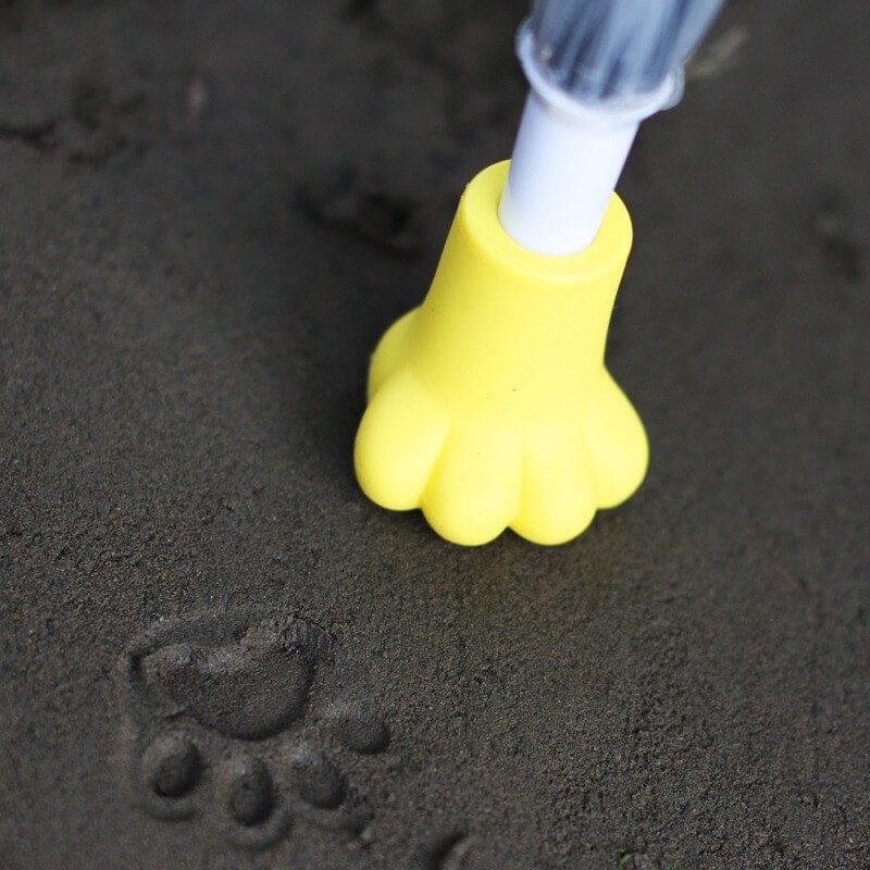傘に装着した肉球キャップで地面に猫の足跡をつけたイメージ