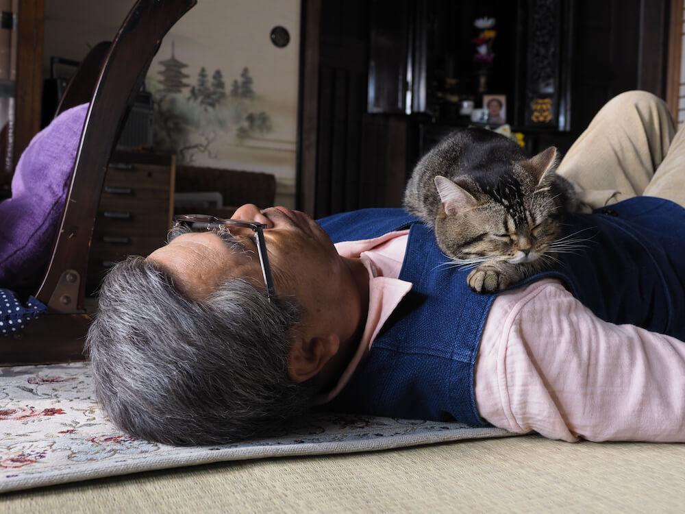 大吉じいちゃんの胸の上で眠る猫のタマ