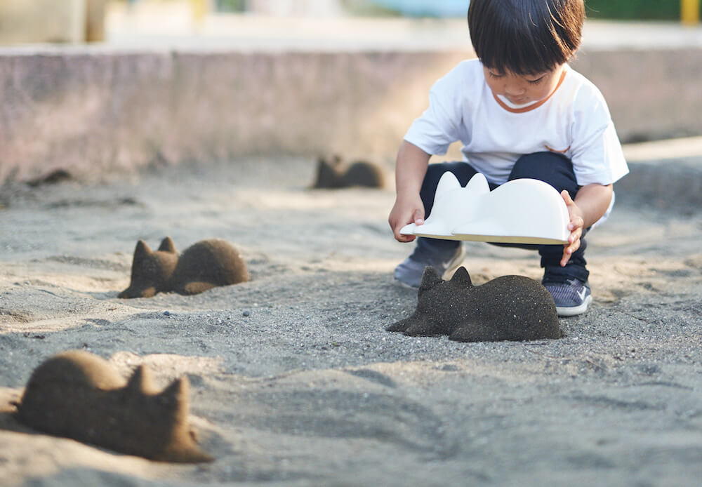 砂場でネコカップを使って立体的な猫シルエット像を作る子供(ネコカップの使用イメージ)