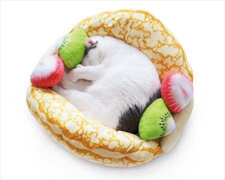 フルーツオムレット型の猫ベッド「にゃんこクレープオムレット」の中で丸まって眠る猫