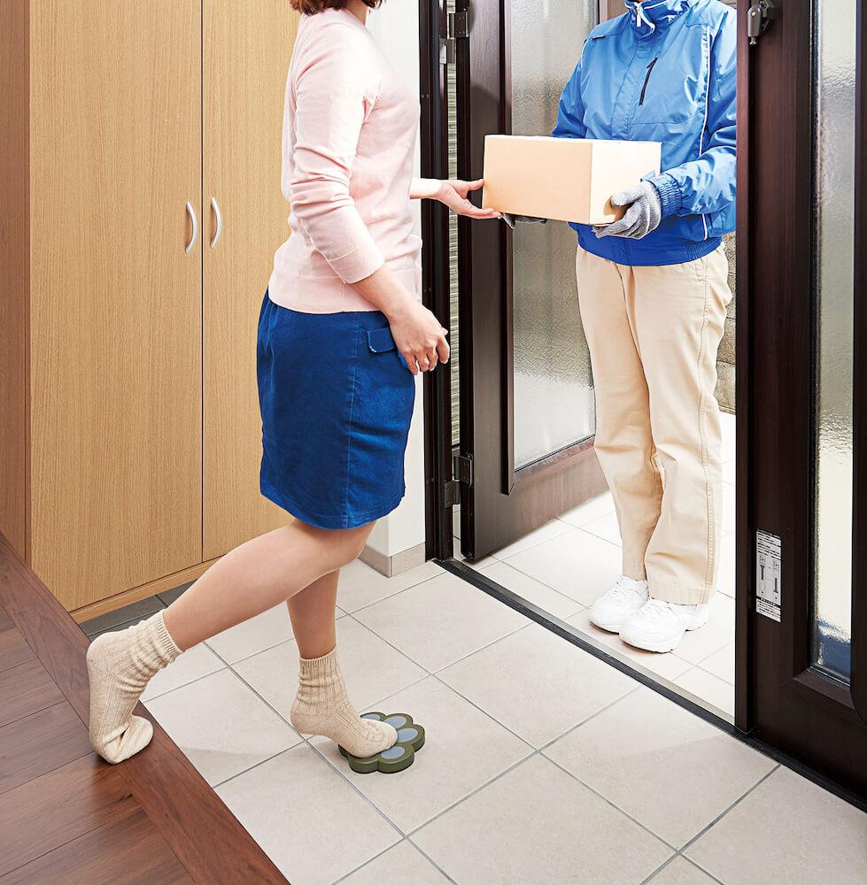 玄関で足裏を汚さずに片足を置ける「玄関のちょい乗り ねこふんじゃった!」に足をのせて宅急便を受取るイメージ