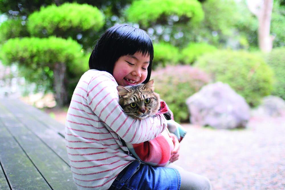 猫を抱きしめる猫庭の館長、手島姫萌さん