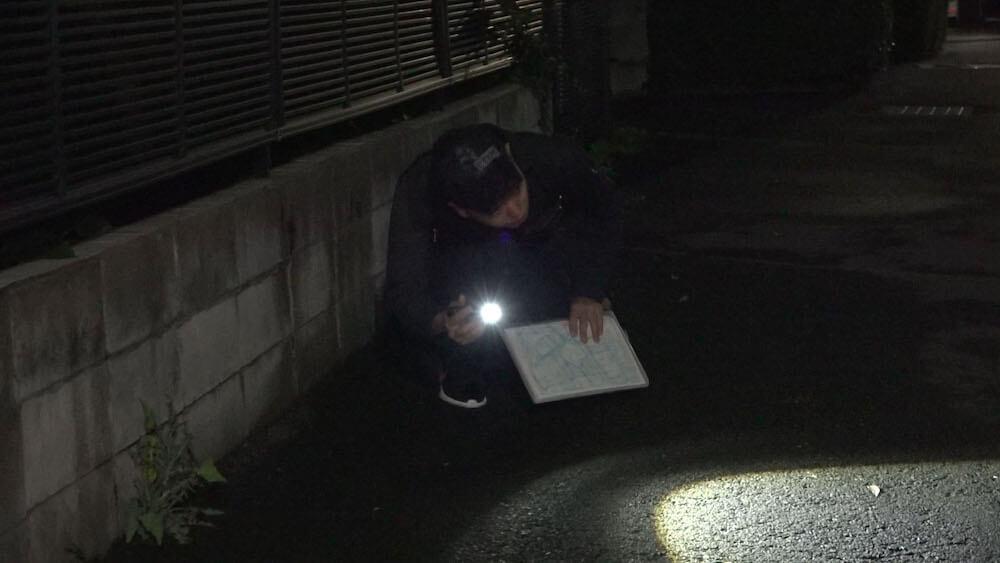 懐中電灯で車の下を照らして猫を探すペット探偵