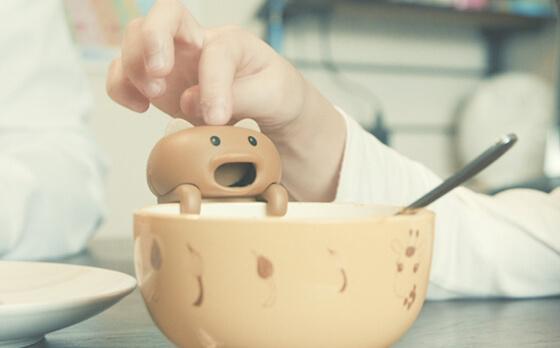猫型ロボット「猫舌フーフー」をカップの縁に掛けて食べ物や飲み物を冷ましているイメージ