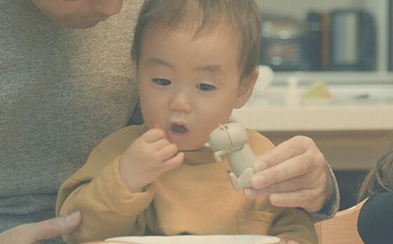 食卓コミュニケーション・トイ「猫舌フーフー」を小さな子供に見せるシーン