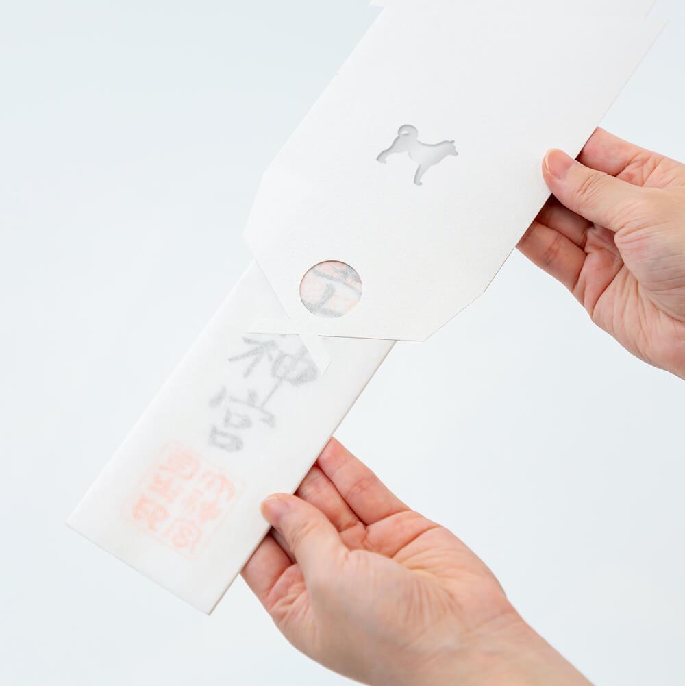 動物のシルエットがデザインされた「貼る神棚 アニマルズ」に神社の御札を封入するイメージ