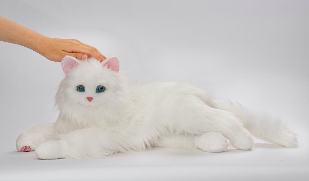 猫型ペットロボット「しっぽふりふり あまえんぼうねこちゃん」が頭を撫でられるイメージ