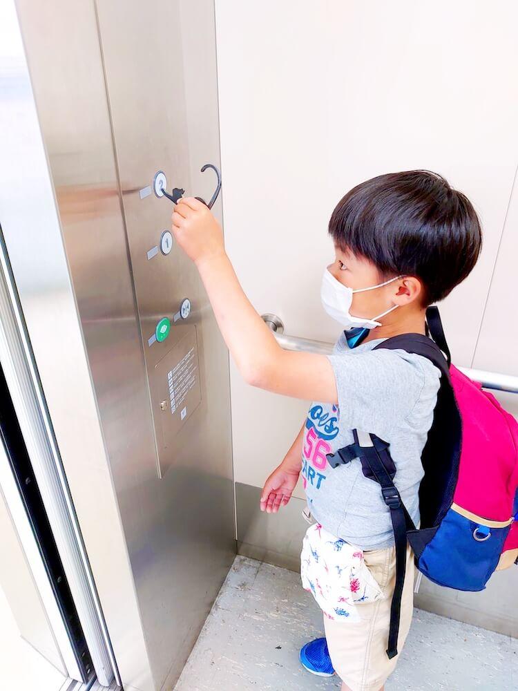 猫型の非接触グッズ「HIBATOUCH(ヒバタッチ)」でエレベーターのボタンを押すシーン