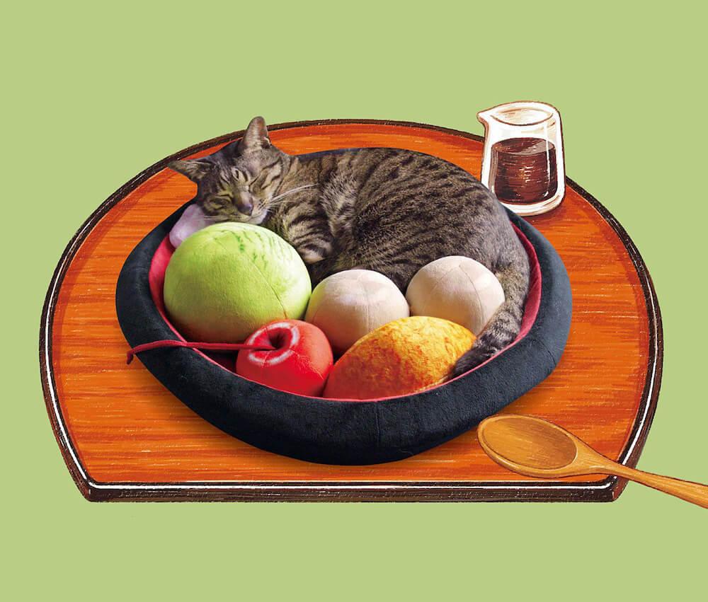 あんみつをモチーフにした猫用ベッド「和のおもてニャし あんみつにゃんこクッション」に猫が寝転んだイメージ