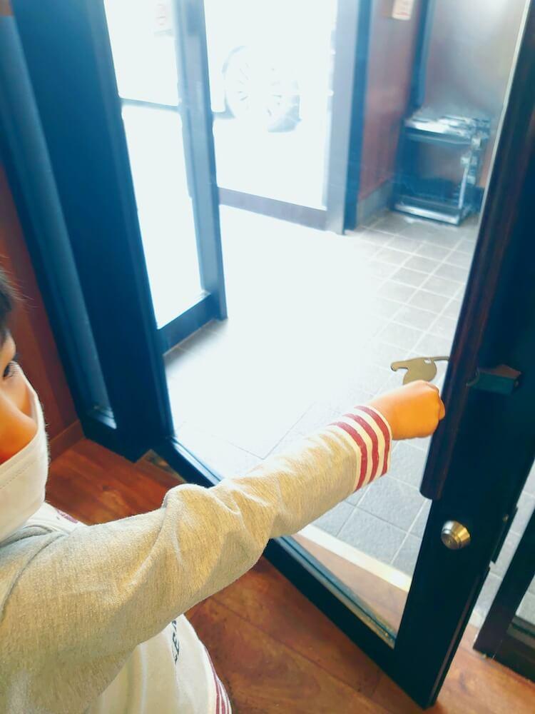 猫型の非接触グッズ「HIBATOUCH(ヒバタッチ)」をドアノブに引っ掛けてドアを開けるシーン