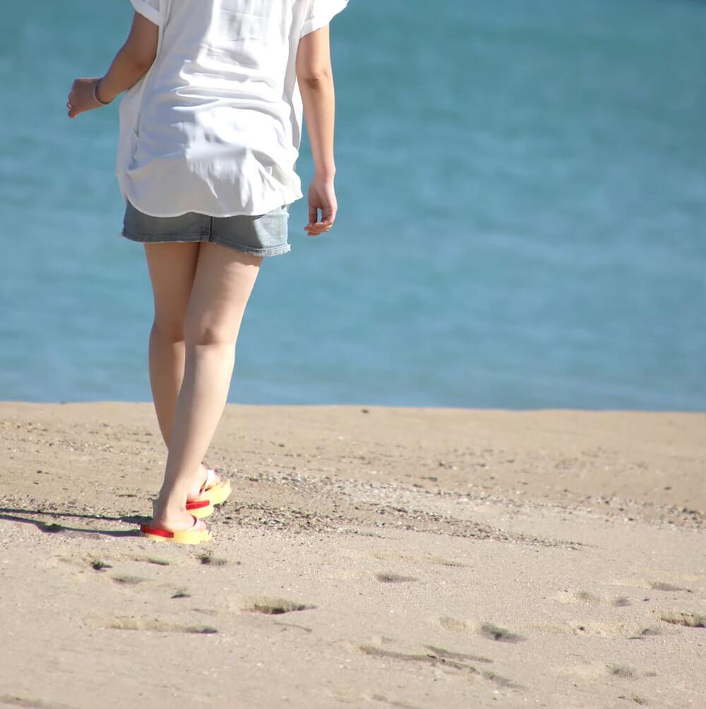 ネコ型のサンダル「にゃらげた」をビーチで履いて歩くイメージ