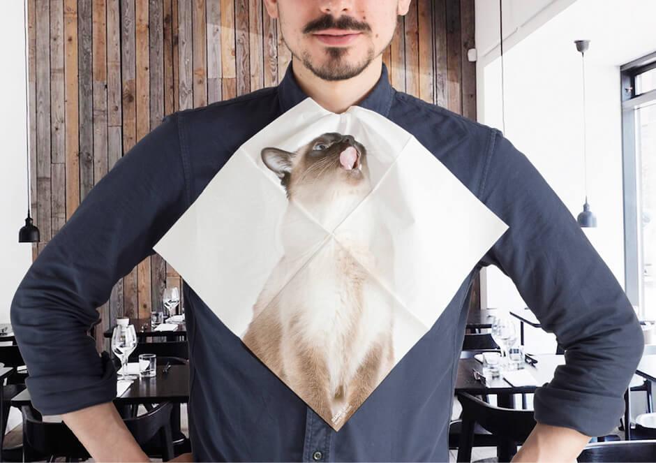 シャム猫の写真がプリントされた紙ナプキン「CAT NAPKINS」を首にかけるイメージ by SUCK UK