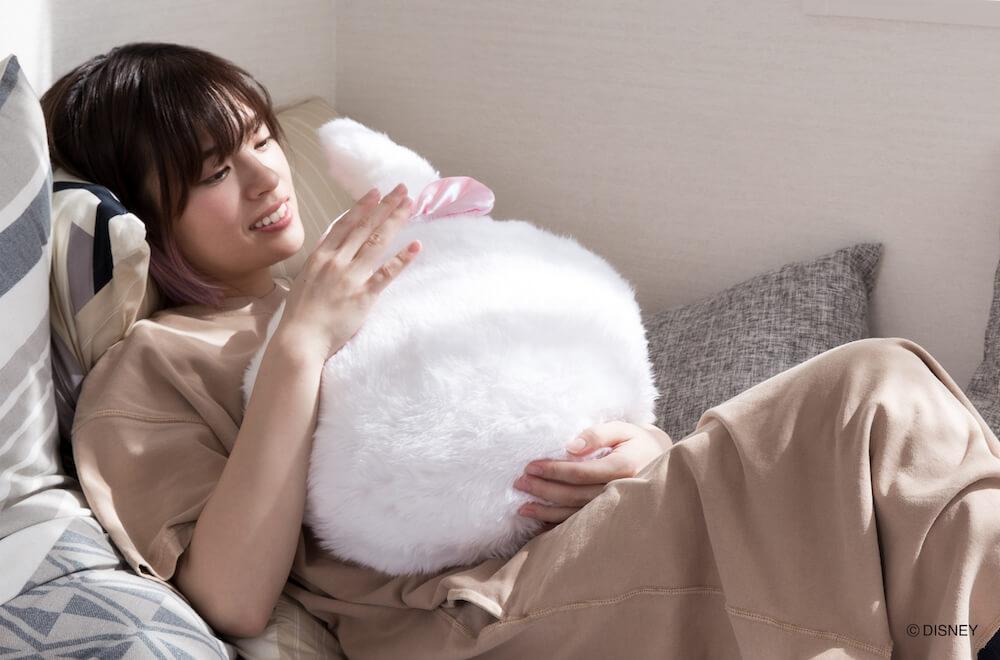 ソファに寝転びながらペットのようにQoobo ディズニーシリーズ「マリー」を可愛がる女性のイメージ