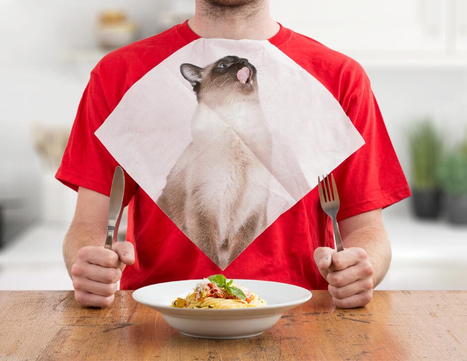 シャム猫の写真がプリントされた紙ナプキン「CAT NAPKINS」を首にかけて食事をするイメージ by SUCK UK
