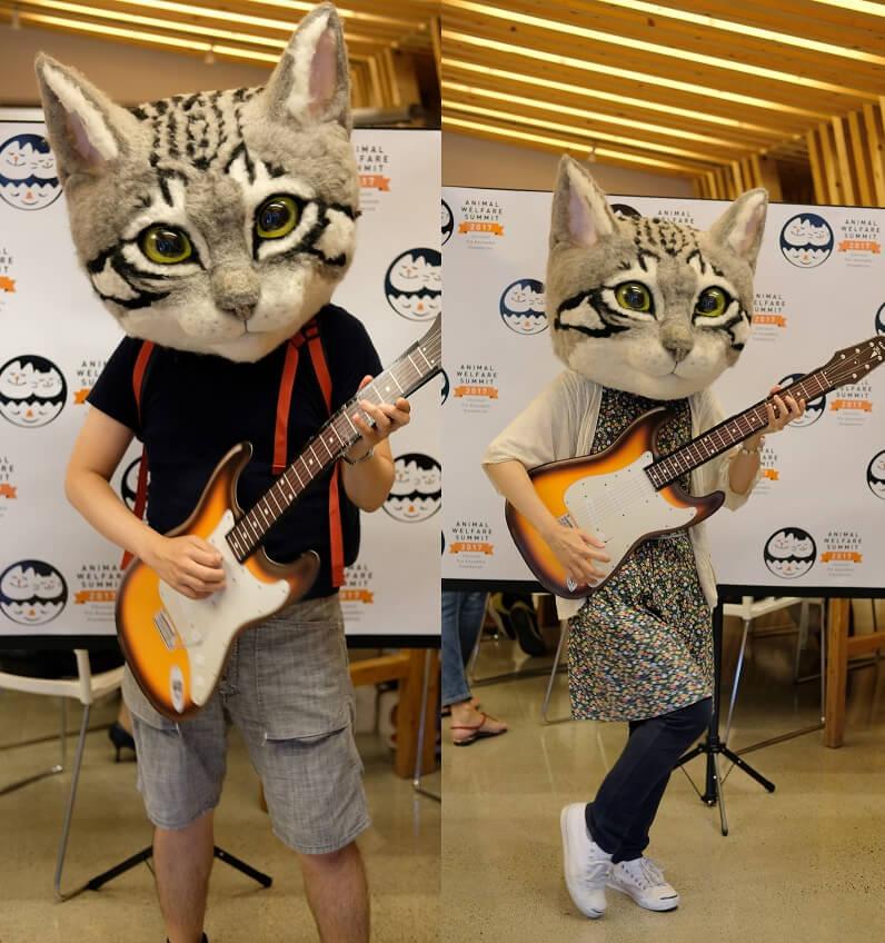 人間の頭がすっぽりと入る等身大サイズのかぶりもの「リアル猫ヘッド」を被ってギターを演奏するイメージ