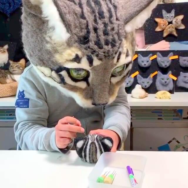巨大猫のかぶりもの「リアル猫ヘッド」を装着して猫の羊毛フェルト作品を作る佐藤法雪氏