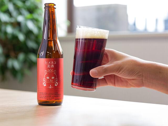 猫がデザインされた地ビール「ヒメネコビール」を注いだグラスを手に持ったイメージ