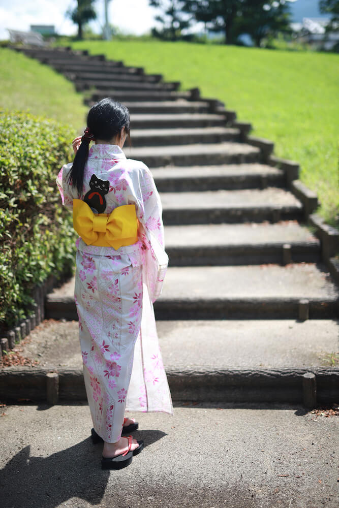 浴衣の帯に「にゃらげた」の猫型うちわを差して歩く女性のイメージ1