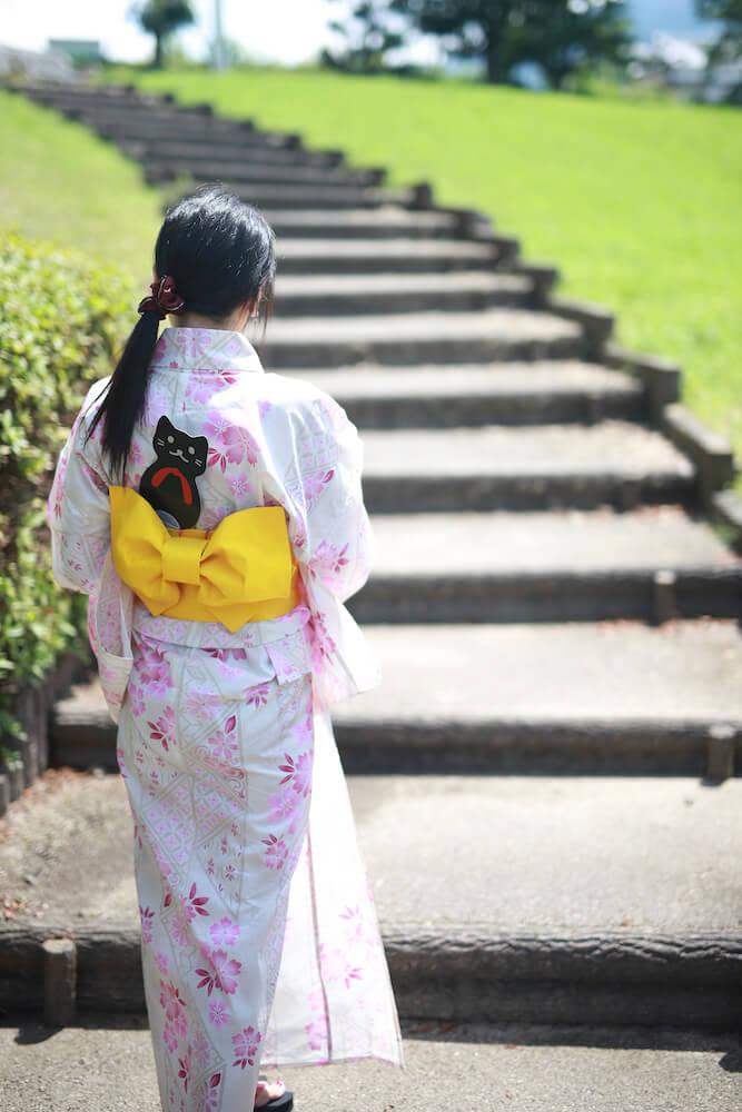 浴衣の帯に「にゃらげた」の猫型うちわを差して歩く女性のイメージ2