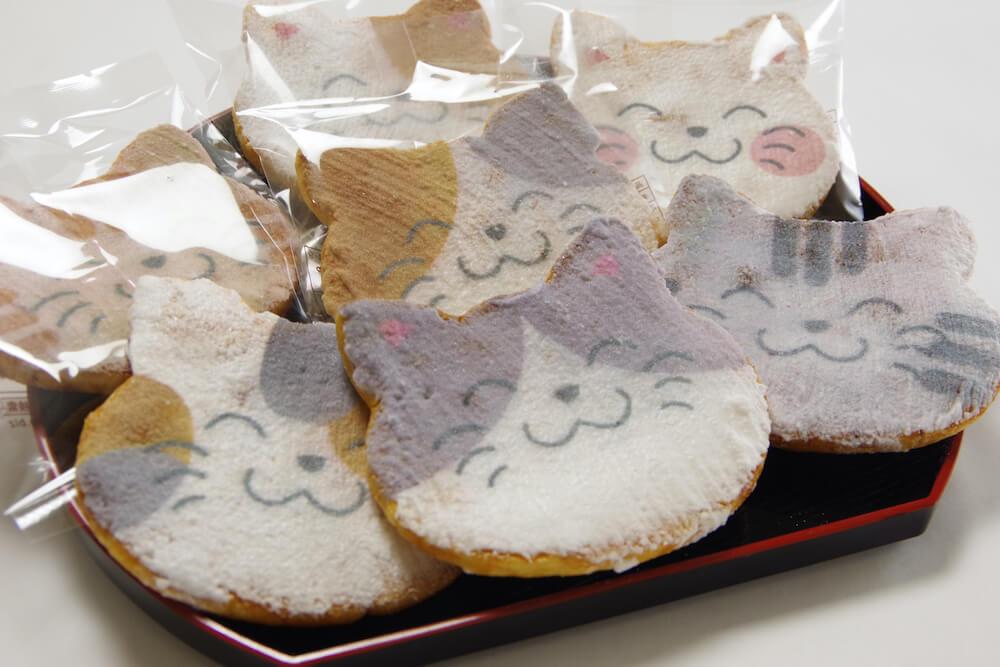 猫の表情や毛並みなどを表現した猫型のおせんべい、福々ねこ煎餅「にゃんべい」の製品イメージ