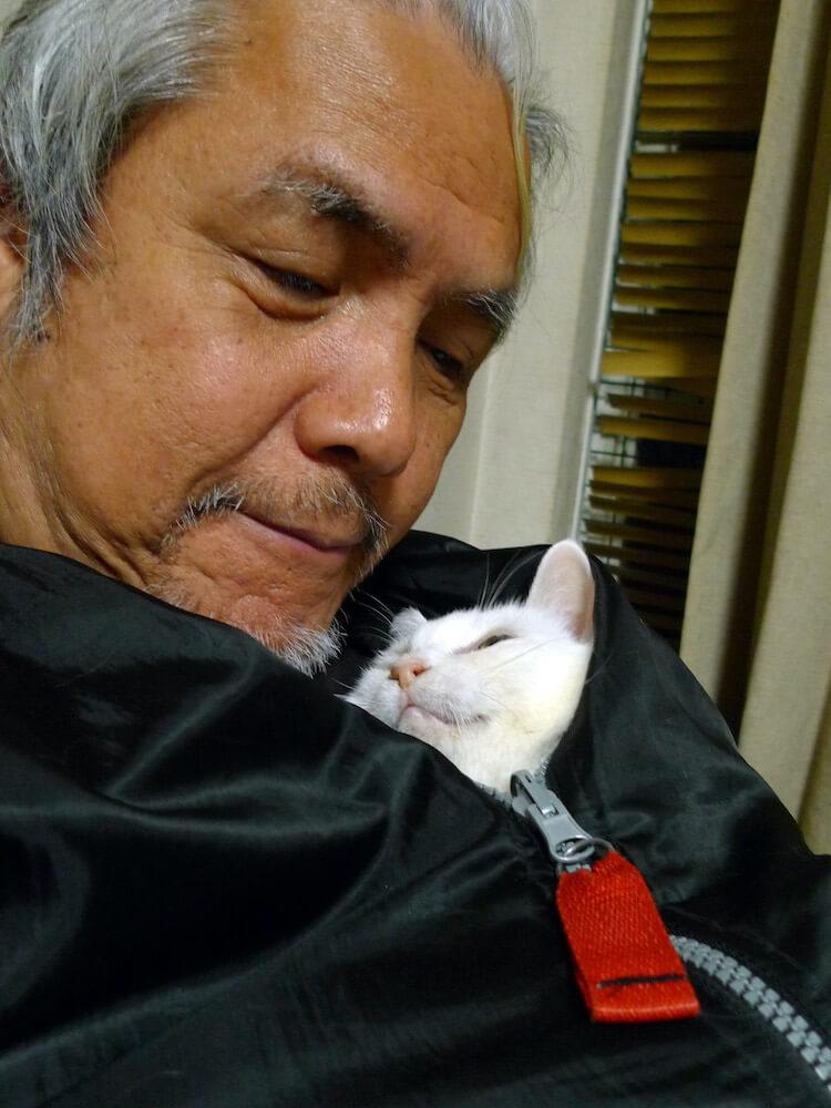 河原猫シロと触れ合うカメラマンの太田康介さん