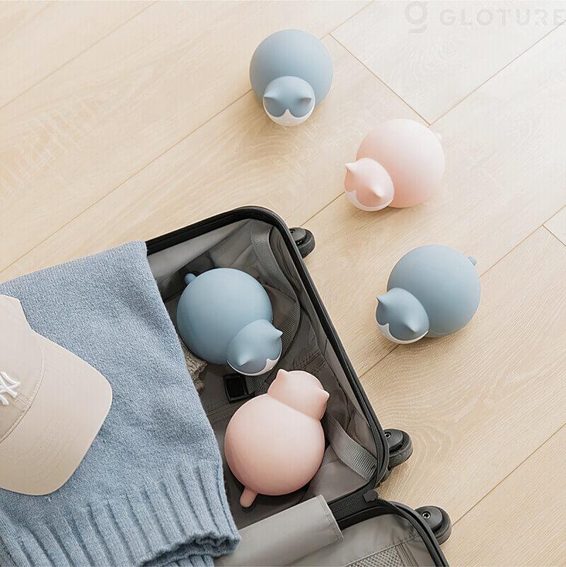 猫型の湯たんぽ「キャットウォーマー」をスーツケースに詰め込むイメージ