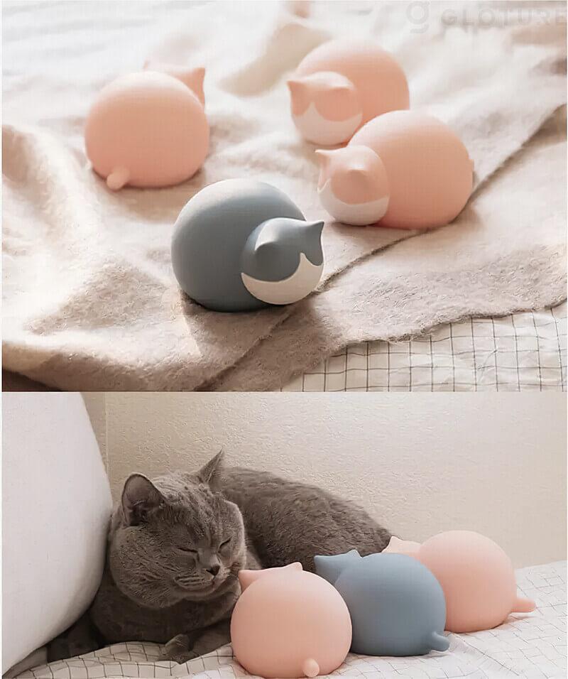 猫型の湯たんぽ「キャットウォーマー」で暖まる猫のイメージ