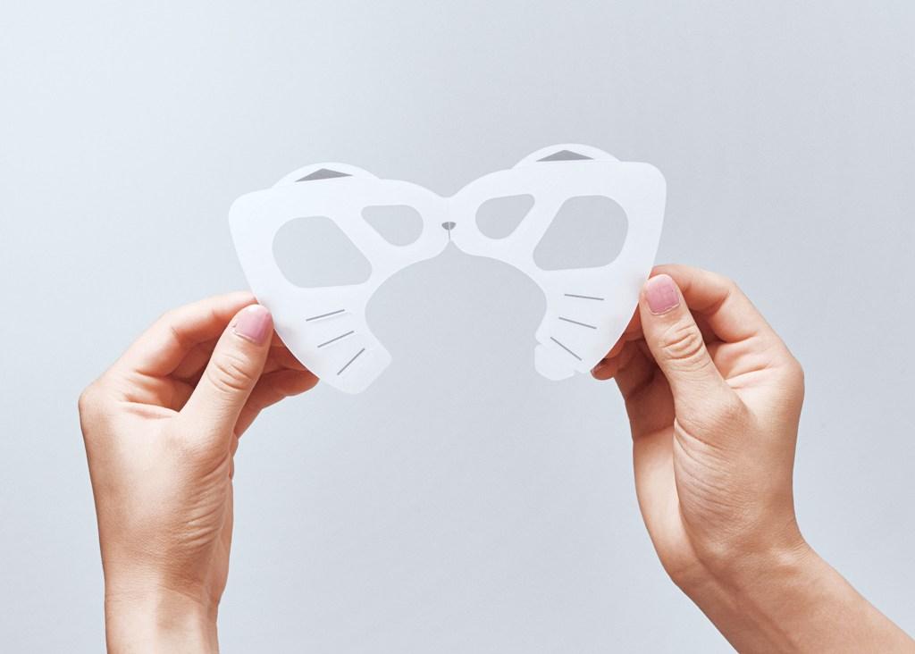 ネコ型のマスクフレーム「にゃんと快適!マスクフレーム」を手に持ったイメージ