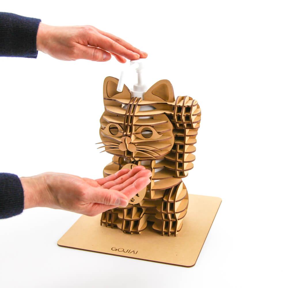 招き猫型の消毒スプレーボトルホルダーの使用イメージ(手を消毒する様子)