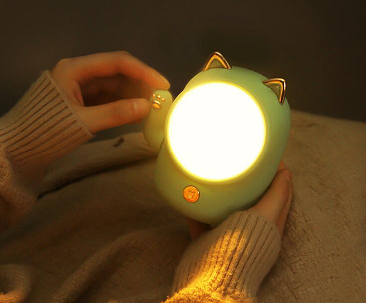 手が動く招き猫型のライトを暗闇で点灯したイメージ