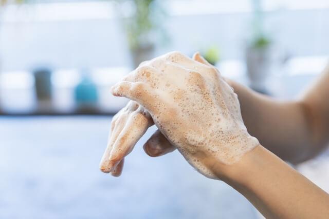 石鹸をつけて手洗いをする女性のイメージ写真