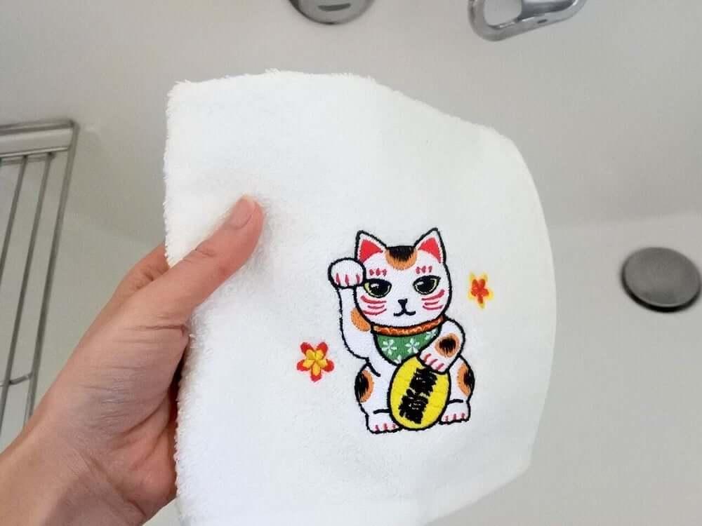 招き猫が刺繍されたハンドタオルで手を拭くイメージ